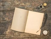 picture of inkwells  - Open diary book and vintage office supplies on wooden table - JPG