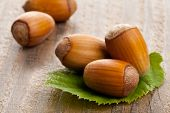 stock photo of hazelnut  - Heap of organic hazelnuts on hazelnut leaf over wood background  - JPG