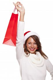 foto of vivacious  - Happy vivacious Christmas shopper wearing a red Santa hat holding up a colorful red shopping bag with a beautiful beaming smile isolated on white with copyspace - JPG