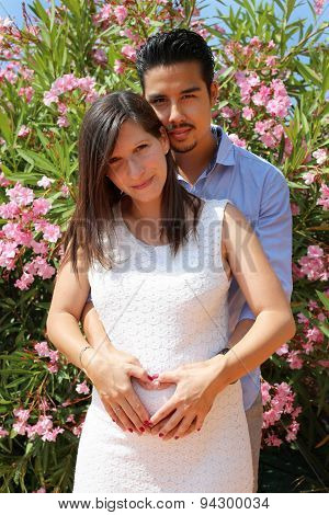 Careful husband is tenderly hugging his pregnant wife and his hands lay on her belly in heart shape