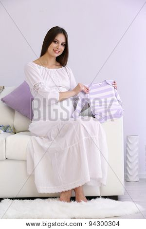 Pregnant woman sitting on sofa with baby's clothes, in room