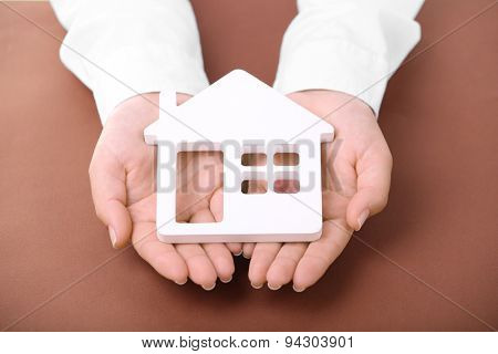 Female hands holding house on color background