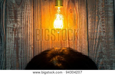 Head with Glowing bulb on the wood background
