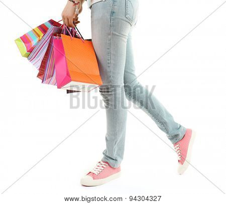 Colorful shopping paper bags in female hand isolated on white