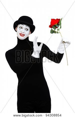 Emotional male mime artist with red rose performing love. Isolated over white.