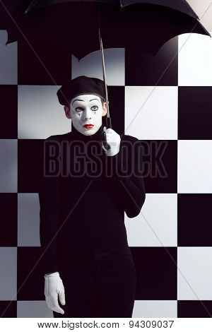 Portrait of a male mime artist standing under umbrella expressing sadness and loneliness. Chess board background.