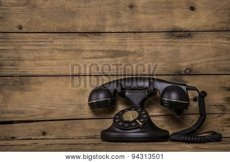 Old black nostalgic phone on brown vintage background for concepts.
