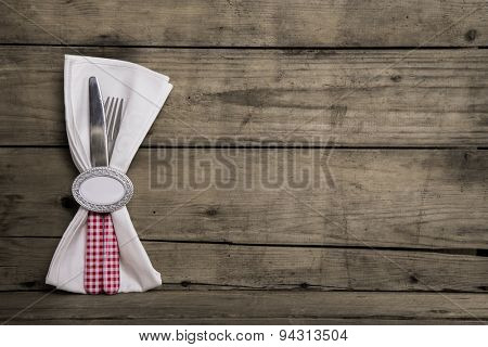 Silver cutlery in red and white checked with napkin on an old wooden background.