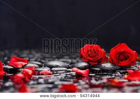Two red rose ,petals with candle and therapy stones