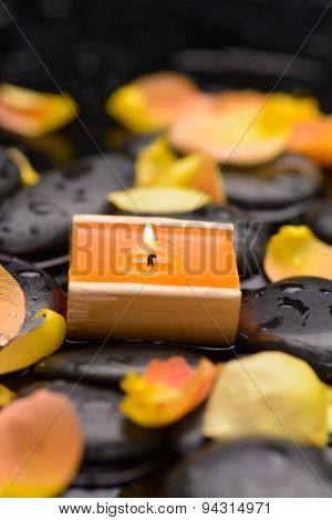 Orange rose petals with candle on wet stones