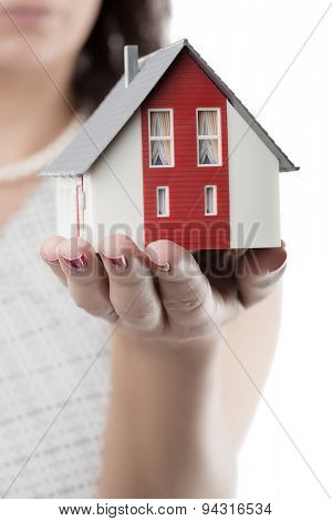 Vertical image of model house in female hand isolated on white background.