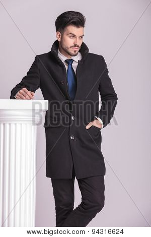 Young elegant business man looking away from the camera while holding one hand in his pocket.