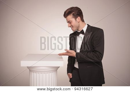 Side view picture of a young business man presenting something on a white column.