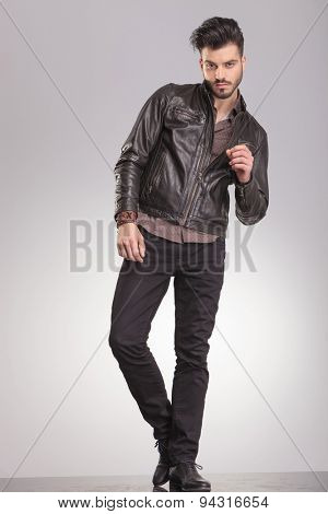 Full length picture of a handsome fashion man posing on grey studio background.