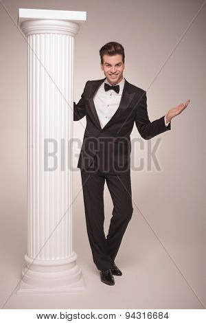 Full body picture of a young elegant business posing with his arms open near a white column.