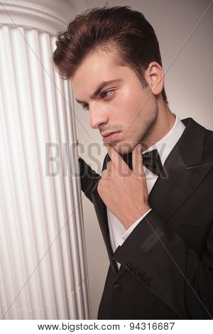 Side view of a handsome business man looking down, thinking while holding his hand to his chin.
