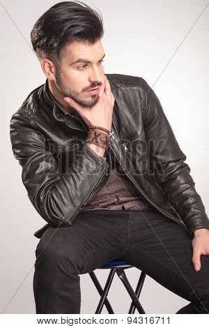 Close up picture of a young fashion man resting on a stool while looking away and holding his hand to the chin.