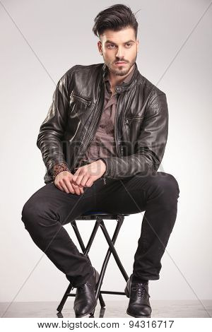 Attractive young casual man looking away from the camera while sitting on a chair.