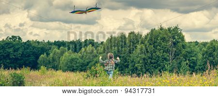 little cute girl flying a kite in a meadow on a sunny day. back view