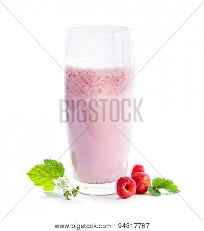 glass of milkshake, berries and green twig of raspberry isolated on white background