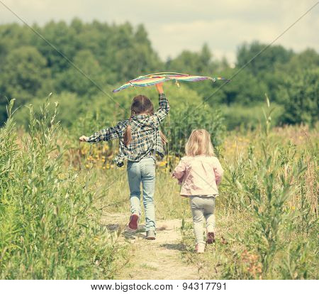 little cute girls flying a kite in a meadow on a sunny day, back view