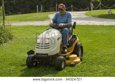Senior Citizen Cutting Grass On A Riding Lawnmower