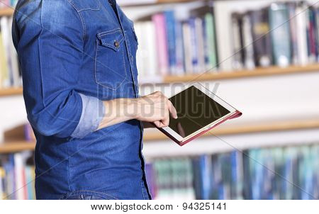 Male student holding a tablet computer at the library