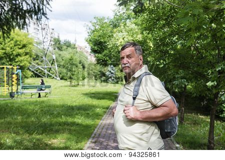 Mature mustached man with a backpack in the alley of the park