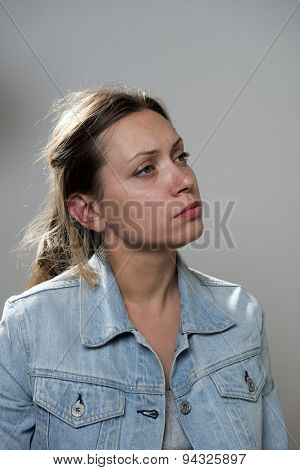 Portert of sad young woman in a denim jacket