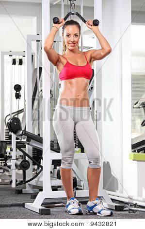 Full Length Portrait Of A Woman Working Out On A Fitness Equipment