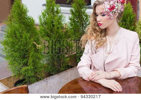 beautiful sweet girl with hair and make-up color bright sitting at a table at an outdoor cafe
