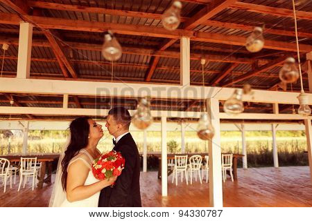 Bride And Groom With Light Bulbs Hanging