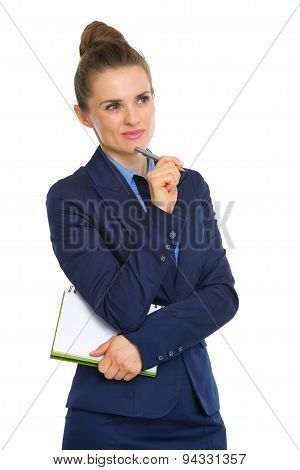 Businesswoman Holding Notebook And Resting Pen On Chin, Thinking