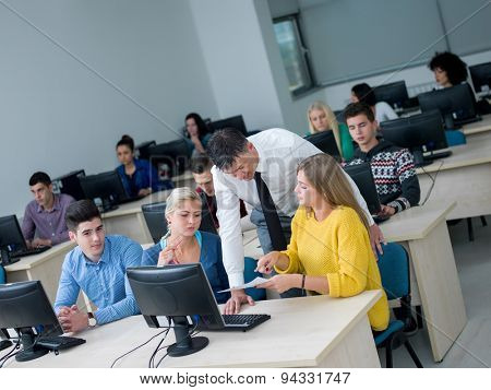 group of students with teacher in computer lab classrom learrning lessons,  get help and support