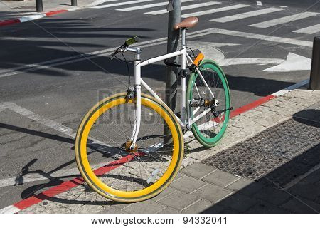 A colored bicycle locked to a post on the pavement
