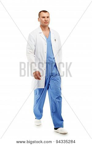 Full Length Portrait Of A Young Male Doctor In A Medical Surgical Blue Uniform In Motion Leaving The