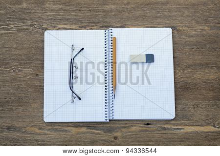 Expand spiral notebook into a cell with a pen, pencil, eraser and glasses, selective focus
