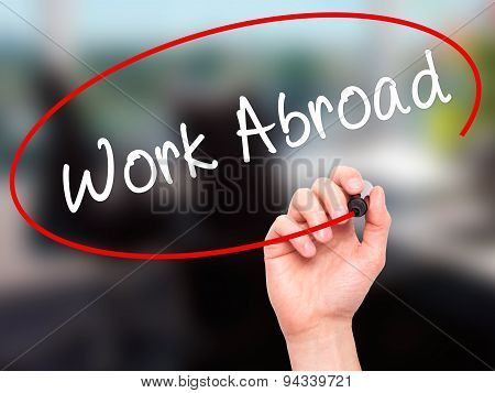 Man Hand writing Work Abroad with black marker on visual screen.