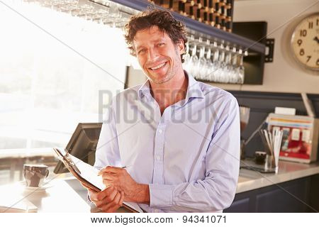 Male restaurant manager holding clipboard, portrait