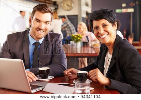 Two business people with laptop meeting in a coffee shop