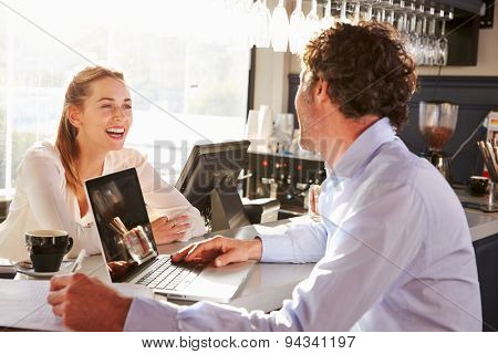 Male restaurant manager with laptop talking to waitress