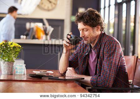 Man at coffee shop, reading digital tablet