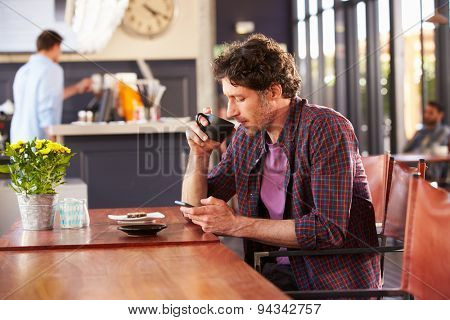 Man at coffee shop, using phone