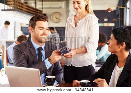 Businessman making payment by phone in a cafe