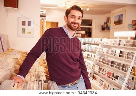 Shop owner posing in a record shop, smiling
