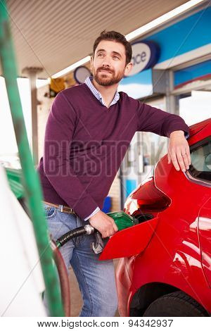 Man refuelling a car at a petrol station