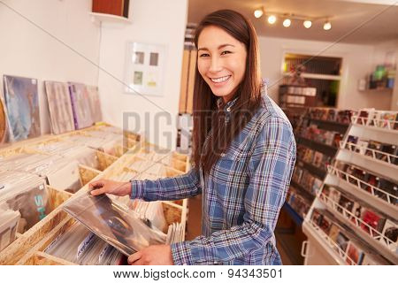Woman selecting a record in a record shop, portrait