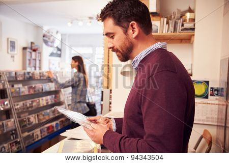 Man working behind the counter at a record shop