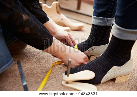Shoemaker measuring customers feet, close up