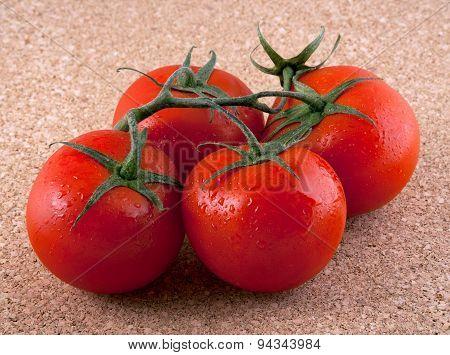 Four Tomatos On A Cork Table